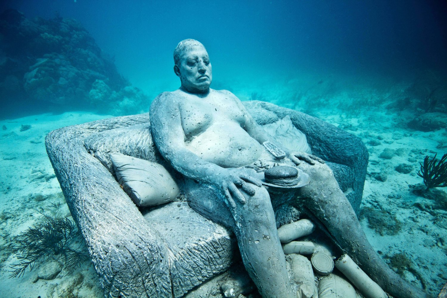 CANCUN, MEXICO - 2011: EXCLUSIVE. New life-sized statues added to the Museo Subacutico de Arte (MUSA) on the sea bed underwater at Cancun and Isla Mujeres National Marine Park in 2011 in Cancun, Mexico. Never-before-seen pictures show the fusion of art and conservation in a artificial reef supporting marine life deep underwater - made from sculptures of real members of the public. Bright tropical fish and agile divers can be seen darting in and out of the huge living art piece that contains hundreds of life-sized statues on the sea bed. Big thinking British artist Jason de Caires Taylor, 36, from Cantebury, Kent captured impressions of real people using 'life casts' and built the installation using materials that will encourage coral to grow. It will produce a coral reef and new home for a variety of aquatic creatures at the Cancun and Isla Mujeres National Marine Park in Mexico. The project, called The Museo Subacutico de Arte (MUSA), aims to ease pressure on natural reefs in the area caused by over half a million water-going tourists who flock to the region every year. (Photo by Jason de Caires Taylor / Barcroft Media / Getty Images)