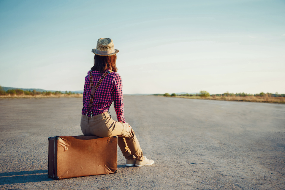 Woman sits on retro suitcase and looks away on road, theme of travel, space for text